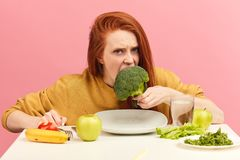 Vegetable diet. Sad dull woman holding broccoli on fork while making grimace royalty free stock photo