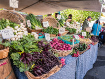 Vegetable display from large local farm at Corvallis Farmers Mar. Baskets of fresh vegetables displayed under tent at Gathering Together Farm booth at Corvallis Stock Photo