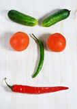 Vegetable face. On the white wooden background stock image