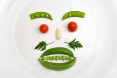 Vegetable face. Made of peas, parsley, tomato and garlic on a white plate royalty free stock images