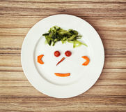 Vegetable face made of cucumber, chilli, tomatoes and carrot on. The white plate. Crazy theme. Teenage funny face stock photo
