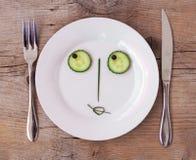 Vegetable Face on Plate - Female, Flirting. Vegetable Face on Plate with knife and fork, set on wooden board - Female, Flirting stock image