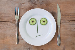 Vegetable Face on Plate - Male, Shocked. Vegetable Face on Plate with knife and fork, set on wooden board - Male, Shocked royalty free stock photo