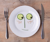Vegetable Face on Plate - Male, Shy. Vegetable Face on Plate with knife and fork, set on wooden board - Male, Shy stock photo