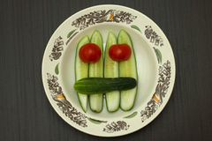 Vegetable face. Smiling face of tomatoes and cucumbers in a dish on a dark table Stock Photography
