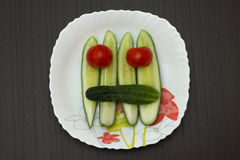 Vegetable face. Smiling face of tomatoes and cucumbers in a dish on a dark table Royalty Free Stock Image
