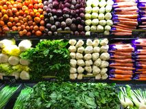 Vegetable Farm Produce on Store Grocery Shelves. Fresh produce of carrots, beets, celery, bok choy, spinach, kale, lemon grass and more line the shelves of Royalty Free Stock Photos