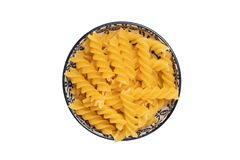 Vegetable food. A bowl of uncooked raw spirelli or noodles isolated on a white background. Healthy eating. Top view with space for royalty free stock photography