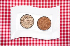 Vegetable food. A decorative white plate with two bowls with buckwheat and quinoa on a red checkered tablecloth. Healthy eating. royalty free stock photo
