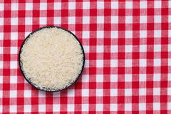 Vegetable food. Macro of a bowl with uncooked raw rice grains on a red checkered tablecloth. Healthy eating. Top view with space stock images