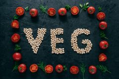 Vegetable frame made of tomatoes and green parsley, dill. Letter shaped garbanzo in middle. Raw vegetarian products. Healthy. Eating concept stock photo
