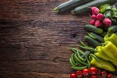 Vegetable.Fresh vegetable tomato radish green pepper peas zucchini and cucumber on rustic oak table Stock Photos