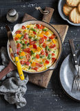 Vegetable frittata in a cast iron skillet on wooden background. Delicious brunch. Top view Royalty Free Stock Image