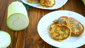 Vegetable fritters made from green zucchini in a plate. On a wooden background stock video