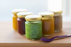 Vegetable or fruit puree or baby food in jars. Baby food, healthy eating and nutrition concept - vegetable or t puree in glass jars and feeding spoon on wooden Stock Image
