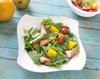 Vegetable and fruit salad arranged in a bowl on a wooden table. Homemade fresh vegan salad with chopped vegetables, fruits, spring greens and spinach. Arranged Stock Image