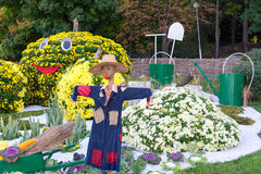 Vegetable garden, guarded by a scarecrow. Big figures made from flowers in the shape of vegetables with colorful chrysanthemums. P Royalty Free Stock Photos