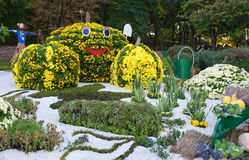 Vegetable garden, guarded by a scarecrow. Big figures made from flowers in the shape of vegetables with colorful chrysanthemums. Parkland in Kiev, Ukraine royalty free stock image