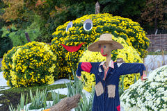 Vegetable garden, guarded by a scarecrow. Big figures made from flowers in the shape of vegetables with colorful chrysanthemums. P Royalty Free Stock Photo
