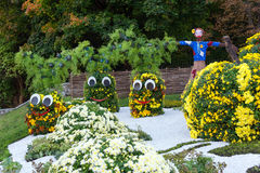 Vegetable garden, guarded by a scarecrow. Big figures made from flowers in the shape of vegetables with colorful chrysanthemums. Parkland in Kiev, Ukraine stock images