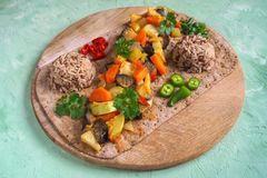 Vegetable garnish of stewed vegetables and wild rice on a round chopping board. Healthy vegetarian food. Vegetable garnish of stewed vegetables and wild rice on royalty free stock photo