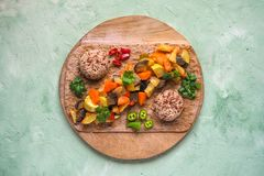 Vegetable garnish of stewed vegetables and wild rice on a round chopping board. Healthy vegetarian food. Vegetable garnish of stewed vegetables and wild rice on stock photo