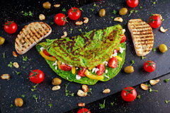 Vegetable Green Omelette with tomatoes, greek cheese, olives, nuts, paprika, toast on stone background. concept healthy royalty free stock photo
