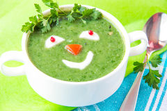 Funny healthy soup with spinach for children royalty free stock photography