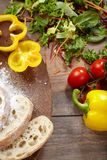 Vegetable ingredients and sliced bread on a cutting board. Vegetable ingredients and sliced bread on a cutting board on a wooden background Royalty Free Stock Image