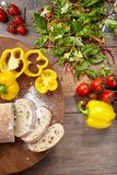 Vegetable ingredients and sliced bread on a cutting board. Vegetable ingredients and sliced bread on a cutting board on a wooden background Royalty Free Stock Photography