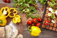 Vegetable ingredients and sliced bread on a cutting board. Vegetable ingredients and sliced bread on a cutting board on a wooden background Stock Images