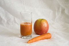 Vegetable juice. Carrots juice in a glass. An apple and carrots Stock Images