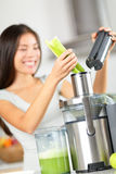 Vegetable juice - woman juicing green vegetables. On juicer machine or juice maker. Healthy raw food concept with person making celery vegetable juice in stock photos