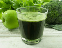 Vegetable juices. Apple and vegetable juices in glass on wood table. for health stock photos