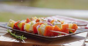Vegetable kabob on plate close up. Close up of various vegetables with wooden kabob sticks next to rosemary sprig sitting on square plate outdoors stock footage