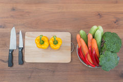 Vegetable, knife and block on wooden table in kitchen Stock Photography