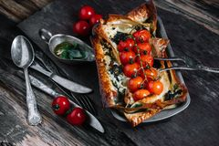 Vegetable lasagna with cherry tomatoes and ingredi. Vegetable lasagna with cherry tomatoes in baking dish and ingredients on dark wood background Royalty Free Stock Image