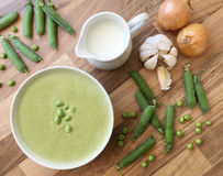 Vegetable legume pea soup and ingredients for cooking. Peas, cream, garlic and onion on wooden table. Top view. Legume pea soup and ingredients for cooking Stock Photography