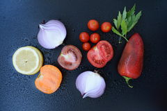 Vegetable and lemon. Red pepper, tomatoes, cherry tomatoes, lovage, onion on dark backround Royalty Free Stock Photo