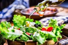 Vegetable lettuce salad. Olive oil pouring into bowl of salad. Italian Mediterranean or Greek cuisine. Vegetarian vegan food Stock Images