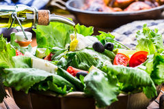Vegetable lettuce salad. Olive oil pouring into bowl of salad. Italian Mediterranean or Greek cuisine. Vegetarian vegan food Royalty Free Stock Image
