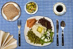 Veggie Lunch on blue checkered table cloth. A vegetable lunch with bread, olives, coffee, carrots, peas, mashed potatoes, lettuce served on a blue checkered Royalty Free Stock Photos