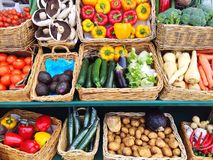 Vegetable market stall. Baskets full of fruit and vegetables including tomatoes and mushrooms on an outdoor market stall royalty free stock image