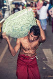 Vegetable market. Worker with heavy sack. A man carrying a heavy bag on his shoulder. The man is shirtless and with traditional Indian clothes. Location stock images