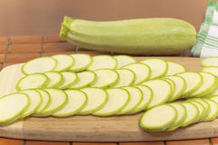 Vegetable marrow sliced ​​into thin mugs. Close-up on chopping board royalty free stock image