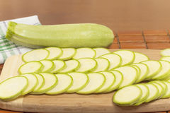 Vegetable marrow sliced ​​into thin mugs. Closeup on chopping board royalty free stock photos