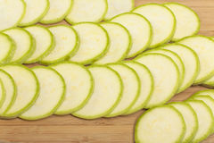 Vegetable marrow sliced ​​into thin mugs. Closeup on chopping board royalty free stock photo