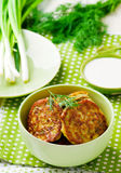 Vegetable marrows fritters with sour cream on a green plate. Stock Photography