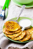 Vegetable marrows fritters with sour cream on a green plate. Stock Photos