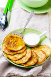 Vegetable marrows fritters with sour cream on a green plate. Stock Images